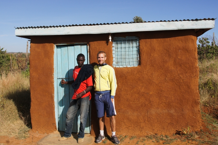 Joel and Nicolas next to the small house that the motorbike financed